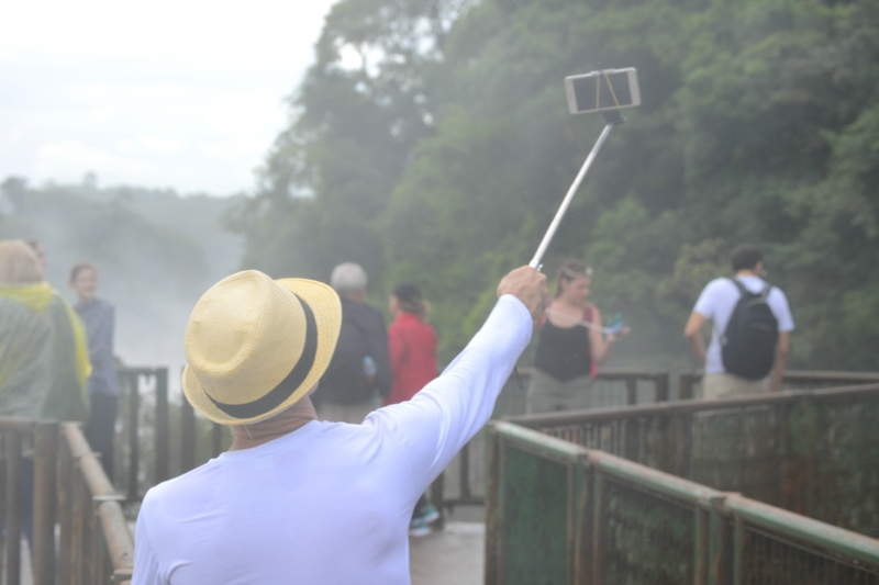 tourist makes selfi overlooking Iguasu waterfalls