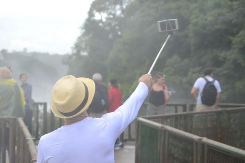 турист делает селфи с видом на водопады Iguasu