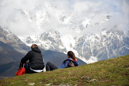 Пара туристов смотрит на гору в Местии, Грузия