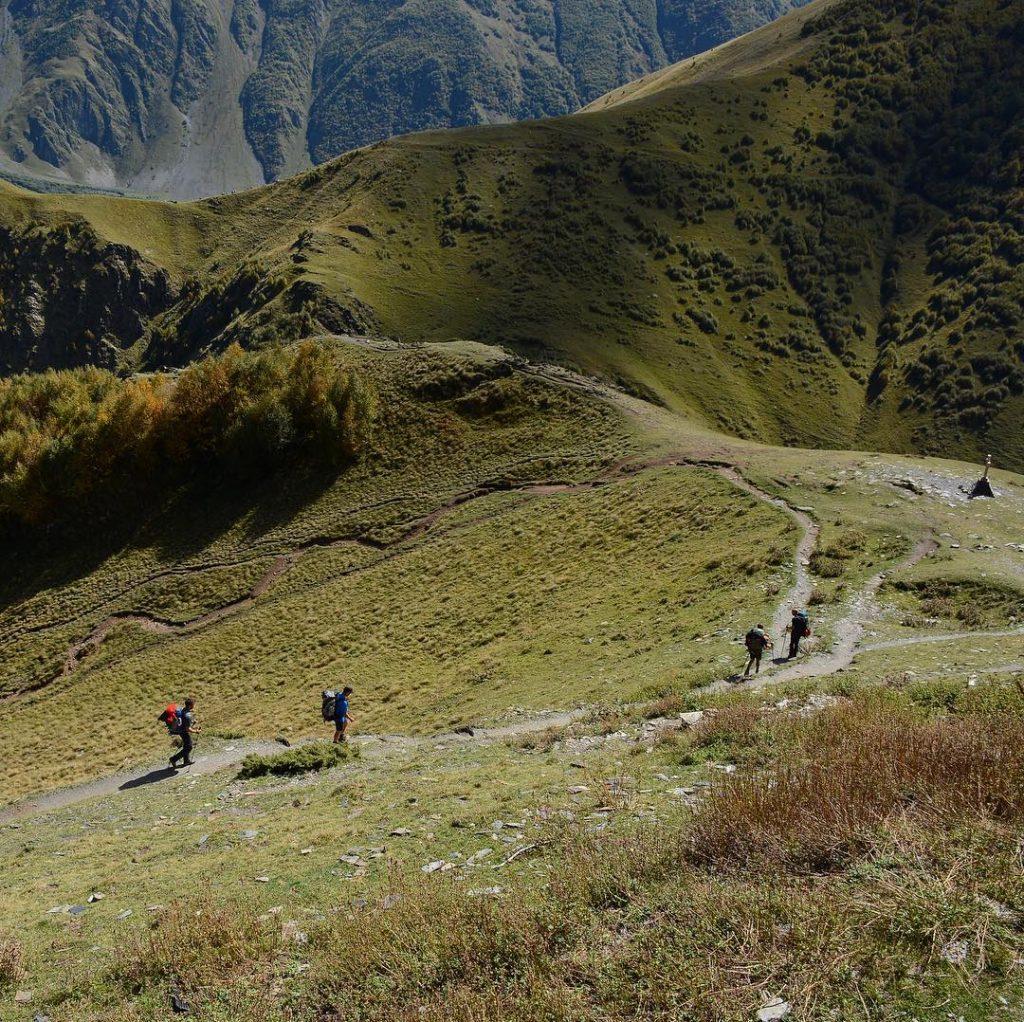 Туристы на пеших маршрутах в горах в районе Троицкой церкви (Гергети) в Казбеги